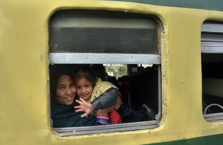 A young passenger from Pakistan waves to media from the Samjhauta Express train as it arrives in Atari, India, Monday, March 4, 2019. A Pakistani railway official said the key train service with neighboring India has resumed in another sign of easing tensions between the two nuclear-armed rivals since a major escalation last week over disputed Kashmir region. (AP Photo/Prabhjot Gill)