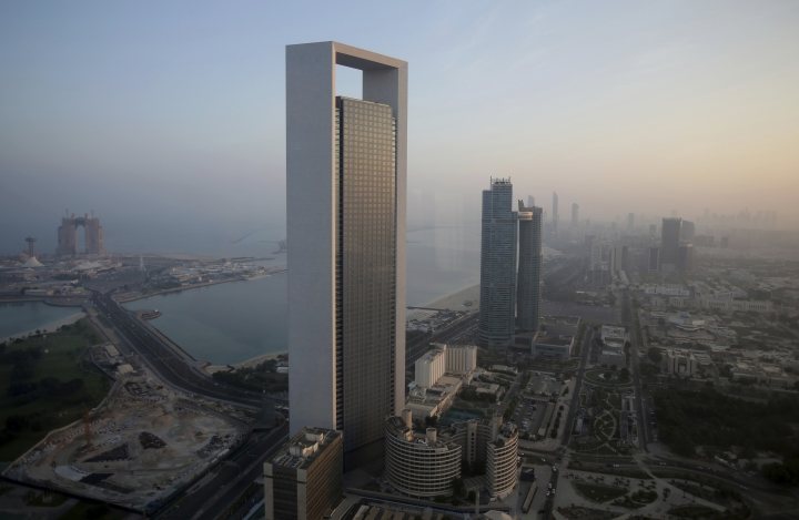 FILE- In this Monday, Nov. 7, 2016, file photo, the sun rises over the skyline in Abu Dhabi, United Arab Emirates. A prominent Dubai bank is warning that non-oil companies across the United Arab Emirates have cut staff at their sharpest rate in nearly a decade amid an economic slowdown. (AP Photo/Kamran Jebreili, File)