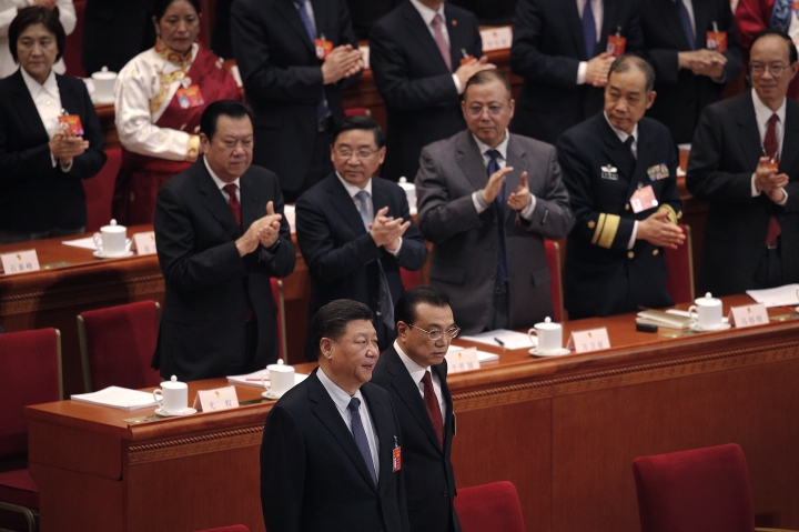 Leaders applaud as Chinese President Xi Jinping, foreground left, and Chinese Premier Li Keqiang, foreground right, arrive at the opening session of the China's National People's Congress at the Great Hall of the People in Beijing, Tuesday, March 5, 2019. (AP Photo/Andy Wong)