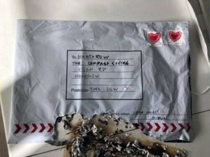 """In this handout photo provided by Sky News, a suspect package that was sent to Heathrow airport and caught fire is seen in England, Tuesday, March 5, 2019. Britain's counter-terrorism police are investigating after three suspicious packages were found in London, including one near City Airport and one near Heathrow Airport. Police said Tuesday all three write postal bags contained yellow bags thought by specialist police to be small improvised explosive devices. Police say the devices """"appear capable of igniting an initially small fire when opened."""" (Sky News via AP)"""