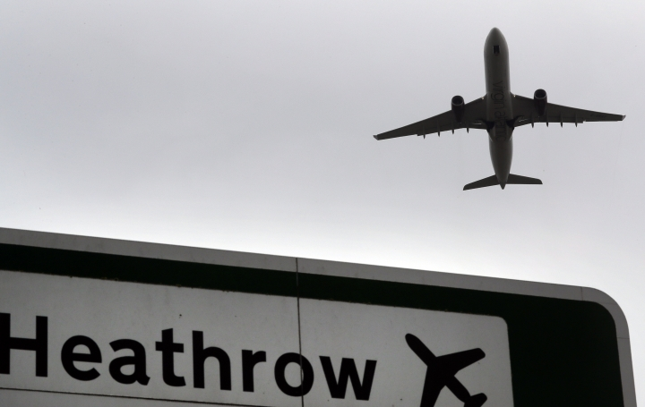 """FILE - In this file photo dated Tuesday, June 5, 2018, a plane takes off over a road sign near Heathrow Airport in London. Britain's counter-terrorism police are investigating after three suspicious packages were found in London, including one near City Airport and one near Heathrow Airport. Police said Tuesday, March 5, 2019 all three write postal bags contained yellow bags thought by specialist police to be small improvised explosive devices. Police say the devices """"appear capable of igniting an initially small fire when opened."""" (AP Photo/Kirsty Wigglesworth, file)"""