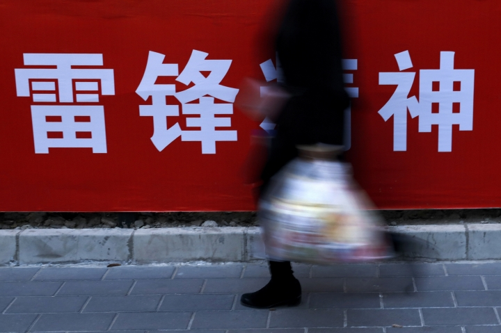 "A woman carries her groceries past a Chinese propaganda board depicting ""Lei Feng Spirit"" on a pavement in Beijing, Tuesday, March 5, 2019. Fast food chain KFC is memorializing a popular Chinese Communist hero with restaurant decor extolling his deeds, in a rare matching of an iconic American brand with Communist propaganda. The official Xinhua News Agency said the company launched its first ""Lei Feng Spirit"" restaurant in Lei's home province of Hunan on Sunday, ahead of Tuesday's official remembrance day for the soldier who died in 1962 at the age of 21. (AP Photo/Andy Wong)"