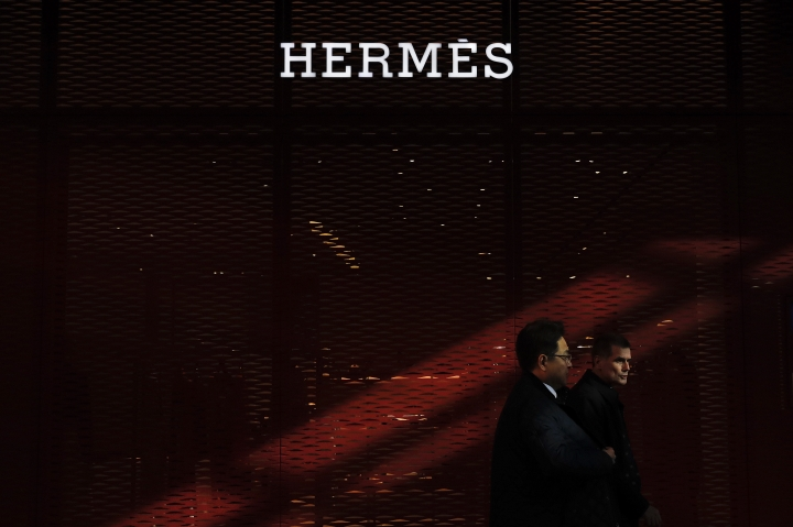 A Chinese and foreign businessmen walk by an Hermes flagship store at the Central Business District in Beijing, Wednesday, March 6, 2019. China will bar government authorities from demanding overseas companies hand over technology secrets in exchange for market share, a top economic official said Wednesday, addressing a key complaint at the heart of the current China-U.S. trade dispute. (AP Photo/Andy Wong)