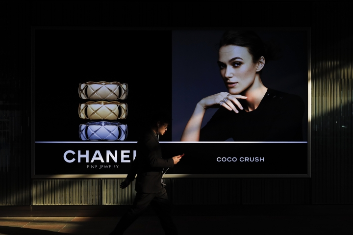 A man browsing his smartphone walks past a Chanel Fine jewelry retail outlet at the Central Business District in Beijing, Wednesday, March 6, 2019. China will bar government authorities from demanding overseas companies hand over technology secrets in exchange for market share, a top economic official said Wednesday, addressing a key complaint at the heart of the current China-U.S. trade dispute. (AP Photo/Andy Wong)