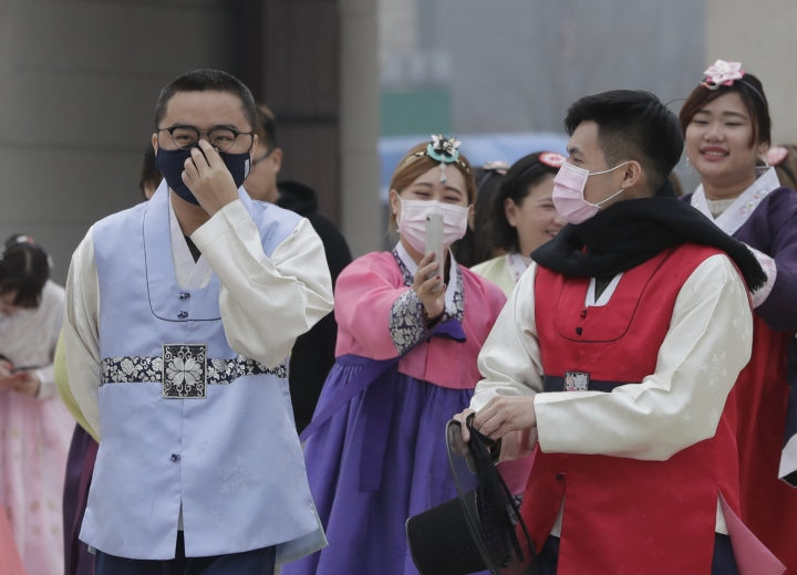 """Foreign visitors dressed in South Korean traditional """"Hanbok"""" attire tour at the Gyeongbok Palace, the main royal palace during the Joseon Dynasty, and one of South Korea's well known landmarks in Seoul, South Korea, Wednesday, March 6, 2019. (AP Photo/Lee Jin-man)"""