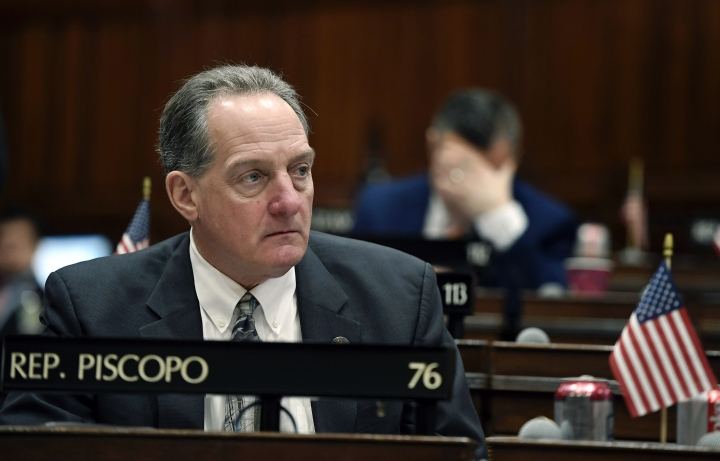 In this Feb. 20, 2019 photo, Connecticut State Rep. John Piscopo, R-Burlington, sits at his desk at the State Capitol in Hartford, Conn. Piscopo has proposed legislation that would eliminate any reference to climate change from the science standards adopted in Connecticut. (AP Photo/Jessica Hill)
