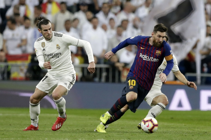Barcelona forward Lionel Messi, right, controls the ball as Real midfielder Gareth Bale looks on during the Spanish La Liga soccer match between Real Madrid and FC Barcelona at the Bernabeu stadium in Madrid, Saturday, March 2, 2019. (AP Photo/Andrea Comas)