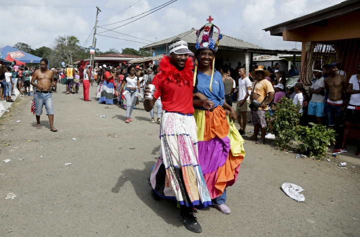"""A woman with a crown who represents the Congo queen walks with a fellow merrymaker during the """"Diablos y Congos,"""" an Ash Wednesday ritual that marks the end of Carnival and the start of the Lenten season in Nombre de Dios, Panama, Wednesday, March 6, 2019. The ritual has been recognized as Intangible Cultural Heritage by UNESCO. (AP Photo/Arnulfo Franco)"""