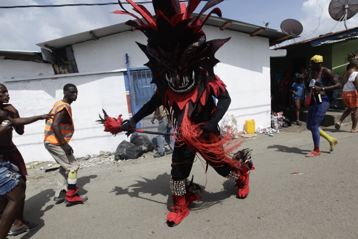 """A man dressed in a devil costume approaches pedestrians during the """"Diablos y Congos,"""" an Ash Wednesday ritual that marks the end of Carnival and the start of the Lenten season in Nombre de Dios, Panama, Wednesday, March 6, 2019. The ritual involves dancers in devil costumes who go about scaring the """"sinners"""" who have been partying for days during carnival. (AP Photo/Arnulfo Franco)"""