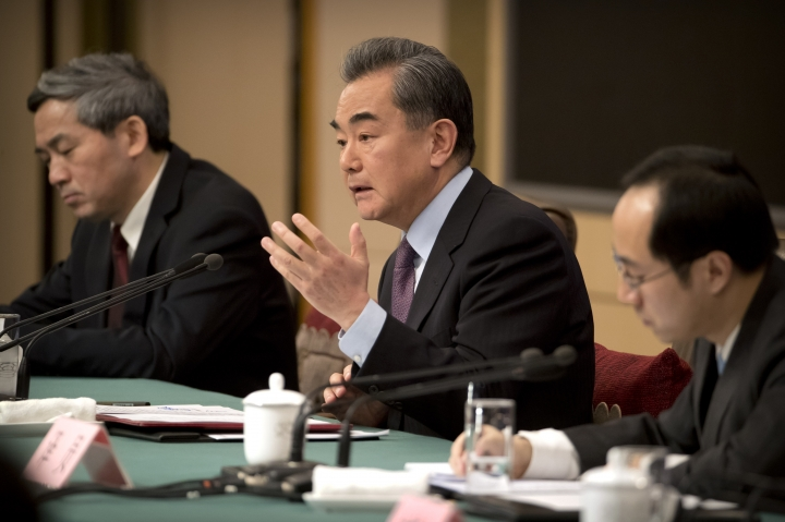 """Chinese Foreign Minister Wang Yi, center, speaks during a press conference on the sidelines of the annual meeting of China's National People's Congress (NPC) in Beijing, Friday, March 8, 2019. China's foreign minister says Beijing will """"take all necessary measures"""" to defend its companies following legal conflicts between tech giant Huawei and the United States. (AP Photo/Mark Schiefelbein)"""