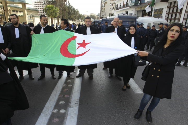 Algerian lawyers carrying their national flag march to the constitutional council in a protest against President Abdelaziz Bouteflika, Thursday March 7, 2019 in Algiers. The Algerian leader, in power since 1999 and all but invisible since a stroke in 2013, is running for a fifth term. (AP Photo/Anis Belghoul)