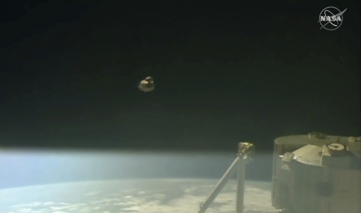 In this image taken from NASA Television, SpaceX's swanky new crew capsule, center, takes off after undocking from the International Space Station, right, Friday, March 8, 2019. The capsule undocked and is headed toward an old-fashioned splashdown. The Dragon capsule pulled away from the orbiting lab early Friday, a test dummy named Ripley its lone occupant. (NASA TV via AP)