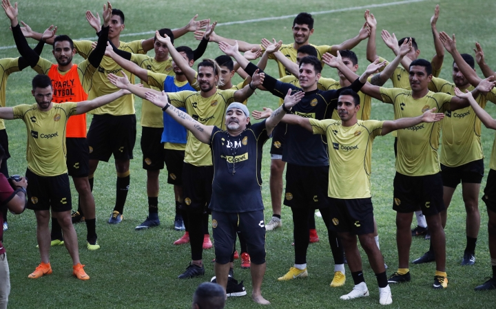 FILE - In this Sept. 10, 2018 file photo, soccer great Diego Maradona and his team sing along with fans in stands, during a training session on the pitch at the Dorados de Sinaloa soccer club stadium, in Culiacan, Mexico. Maradona's lawyer said Friday, March 8, 2019, that the former soccer star will legally recognize three children that he fathered in Cuba. (AP Photo/Marco Ugarte, File)