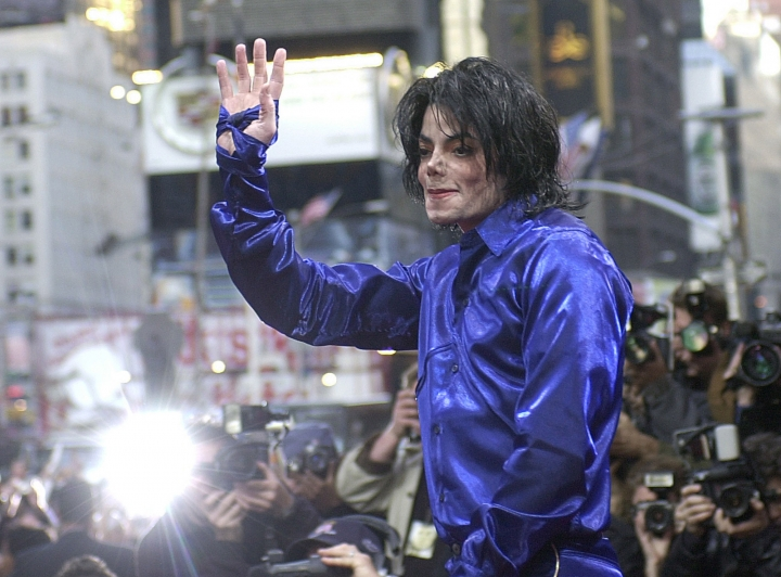 "FILE - This Nov. 7, 2001 file photo, Michael Jackson waves to crowds gathered to see him at his first ever in-store appearance in New York. The producers of ""The Simpsons"" are removing a classic episode that featured the voice of Michael Jackson. Executive producer James L. Brooks told The Wall Street Journal on Thursday, March 7, 2019, ""it feels clearly the only choice to make."" He said fellow executive producers Matt Groening and Al Jean are ""of one mind on this."" (AP Photo/Suzanne Plunkett)"