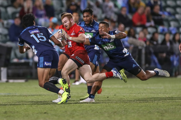 Sunwolves Jamie Booth, center, breaks away from the pack during the Super Rugby match between the Blues and the Sunwolves in Auckland, New Zealand, Saturday, March 9, 2019. (Shane Wenzlick/Photosport via AP)