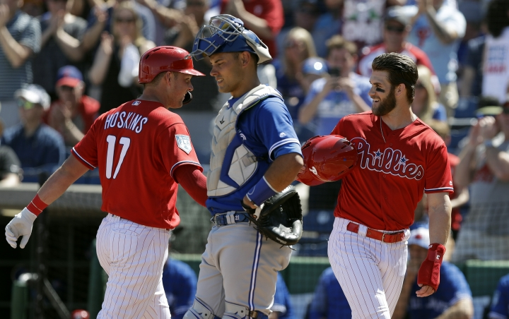 Philadelphia Phillies' Bryce Harper, right, celebrates with Rhys Hoskins, left, after Hoskins hit a two-run home run off Toronto Blue Jays pitcher Matt Shoemaker during the first inning of a spring training baseball game Saturday, March 9, 2019, in Clearwater, Fla. Looking on is Blue Jays catcher Luke Maile. (AP Photo/Chris O'Meara)