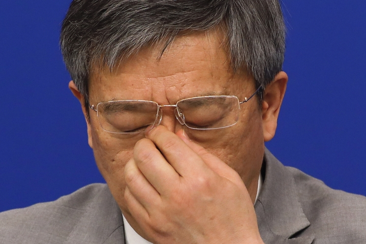 China's Central Bank Governor Yi Gang reacts during a press conference on the sideline of the National People's Congress at the media center in Beijing, Sunday, March 10, 2019. (AP Photo/Andy Wong)