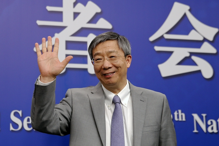 China's Central Bank Governor Yi Gang waves as he arrives for a press conference on the sideline of the National People's Congress at the media center in Beijing, Sunday, March 10, 2019. (AP Photo/Andy Wong)
