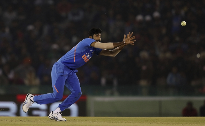India's Jasprit Bumrah stops the ball during the fourth one day international cricket match between India and Australia in Mohali, India, Sunday, March 10, 2019. (AP Photo/Altaf Qadri)