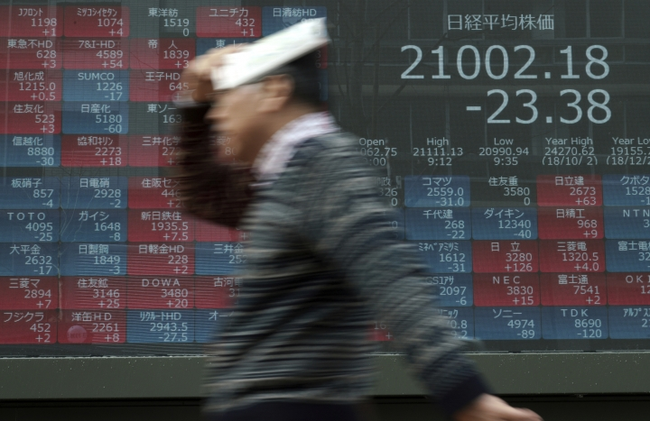 A man walks in the rain past an electronic stock board showing Japan's Nikkei 225 index at a securities firm in Tokyo Monday, March 11, 2019. Shares were mixed in Asia on Monday as investors awaited further developments in trade talks between the U.S. and China. (AP Photo/Eugene Hoshiko)