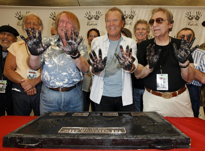 FILE - In this June 25, 2008, file photo, Don Randi, from left, Glen Campbell and Hal Blaine, representing session musicians known as The Wrecking Crew, hold up their hands after placing them in the cement following the induction ceremony for Hollywood's RockWalk in Los Angeles. Drummer Blaine, who played on many of the biggest hits in music history, has died. Blaine's son-in-law Andy Johnson tells The Associated Press that Blaine died of natural causes Monday, March 11, 2019, at his home in Palm Desert, California. He was 90. (AP Photo/Kevork Djansezian, File)