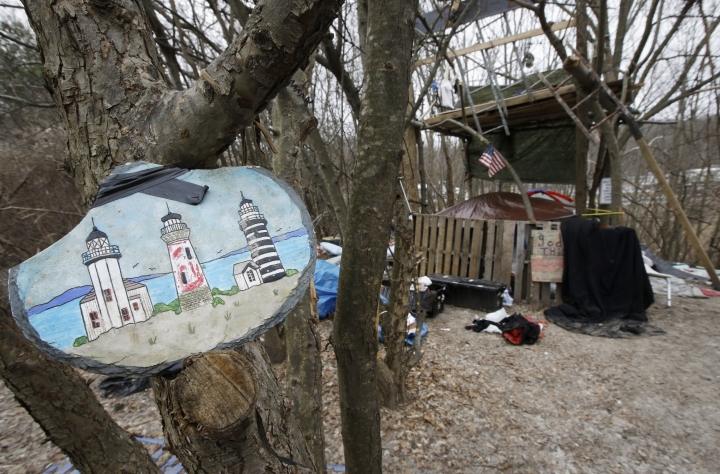 """In this Tuesday, Feb. 12, 2019 photo a decorative plaque featuring lighthouses is attached to a tree near a makeshift shelter in a wooded area, in Worcester, Mass. This industrial city in central Massachusetts has had many nicknames through the years, including """"the Heart of the Commonwealth"""" and """"Wormtown."""" Among them was this less-known medical moniker: """"Hepatitisville."""" (AP Photo/Steven Senne)"""