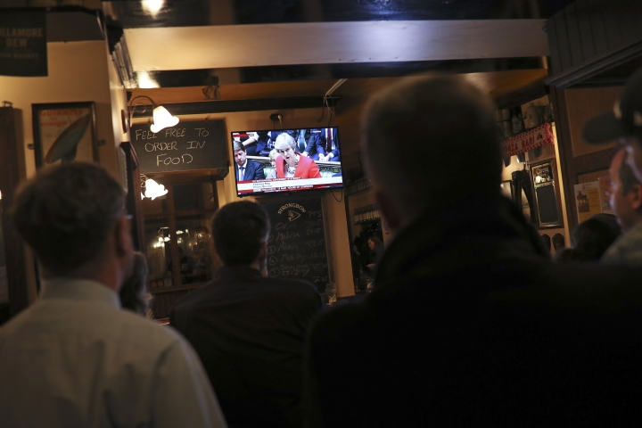 People watch a television in a pub showing Britain's Prime Minister Theresa May during a vote of Brexit deal at the House of Commons, in Brussels, Tuesday March 12, 2019. In an Irish pub in the Belgian capital, a group of Brexit opponents has gathered to watch British lawmakers vote on their country's future in the European Union. (AP Photo/Francisco Seco)