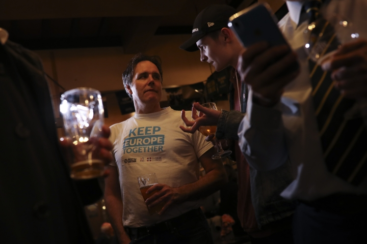 A group of anti-Brexit supporters watch a television in a pub showing the vote of Theresa May's Brexit deal at the House of Commons, in Brussels, Tuesday March 12, 2019. In an Irish pub in the Belgian capital, a group of Brexit opponents has gathered to watch British lawmakers vote on their country's future in the European Union. (AP Photo/Francisco Seco)