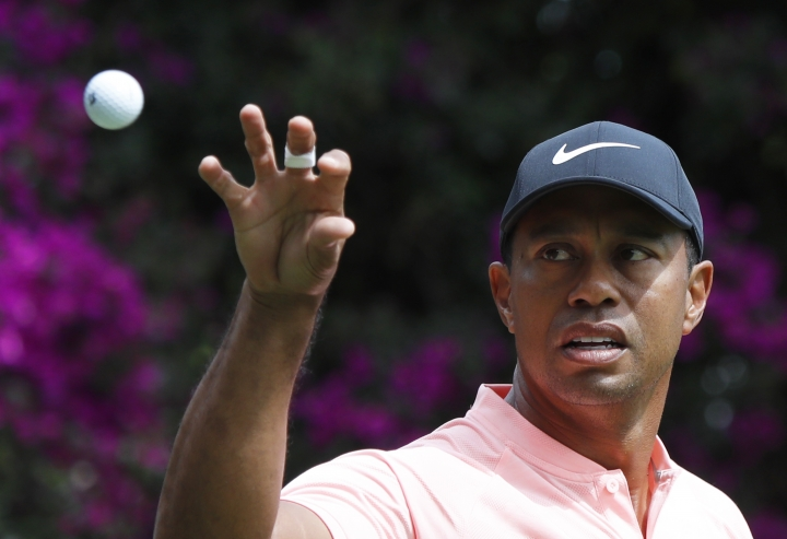 "FILE - In this Feb. 22, 2019, file photo, Tiger Woods prepares to catch a ball tossed by his caddied on the second day of competition of the WGC-Mexico Championship golf tournament at the Chapultepec Golf Club in Mexico City. Woods says a sore neck that kept him out of Bay Hill last week is no longer painful. Woods says his job is to make sure to stay fit and flexible. He used the word ""pliable"" three times during his news conference at The Players Championship. (AP Photo/Marco Ugarte, File)"