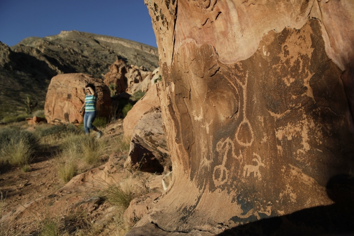 FILE - In this May 26, 2017, file photo, Susie Gelbart walks near petroglyphs at the Gold Butte National Monument near Bunkerville, Nev. As Democrats in Congress prepare to scrutinize President Donald Trump's review of 27 national monuments, most of the recommendations made by ex-Interior Ryan Zinke remain unfinished, seemingly stuck on the backburner as other matters consume the White House. Zinke recommended cuts to the boundaries of Gold Butte National Monument to free up a water district that he thought shouldn't have been included in the boundaries. (AP Photo/John Locher, File)