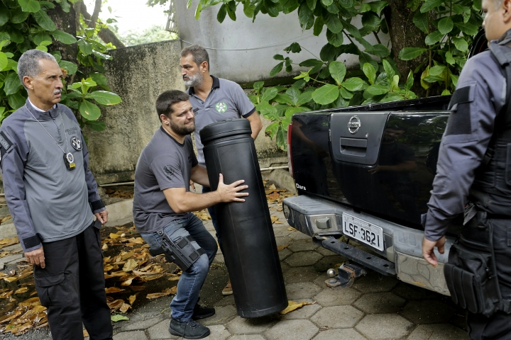 A Civil Police officer carries a case confiscated from the home of suspects in the killing of councilwoman Marielle Franco at the Civil Police headquarters in Rio de Janeiro, Brazil, Tuesday, March 12, 2019. Police in Brazil arrested two suspects in the killing of Franco and her driver. The brazen assassination of the two on March 14 last year led to massive protests and widespread anger in Latin America's largest nation. (AP Photo/Silvia Izquierdo)