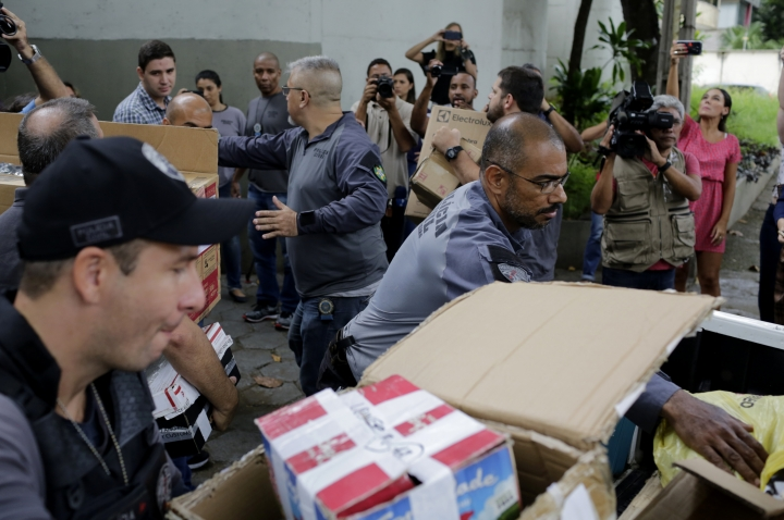 Policemen unload items at Civil Police headquarters in Rio de Janeiro, Brazil, Tuesday, March 12, 2019, that were confiscated from the home of the suspects in the killing of councilwoman Marielle Franco. The brazen assassination of the councilwoman and her driver on March 14 last year led to massive protests and widespread anger in Latin America's largest nation. Two suspects have been arrested. (AP Photo/Silvia Izquierdo)