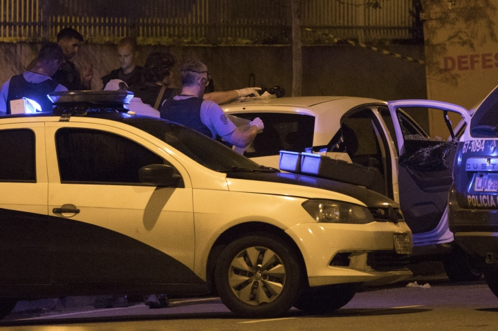 FILE - In this March 14, 2018 file photo, Brazilian police officers work on a crime scene as they stand next to vehicle in which council member Marielle Franco and her driver where both shot to death by two unidentified attackers in Rio de Janeiro, Police in Brazil said on Tuesday, March 12, 2019, that they have arrested two suspects in the killing of Franco and her driver last year. (AP Photo/Leo Correa, File)