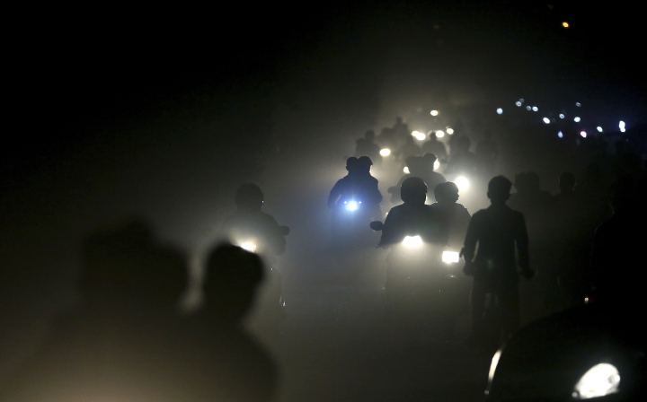 FILE - In this Friday, Nov. 10, 2017 file photo, motorists ride through a thick blanket of smog and dust on the outskirts of New Delhi, India., with microscopic particles spiking at times to 75 times the level considered safe by the World Health Organization. According to a scientific report from the United Nations released on Wednesday, March 13, 2019, climate change, a global major extinction of animals and plants, a human population soaring toward 10 billion, degraded land, polluted air, and plastics, pesticides and hormone-changing chemicals in the water are making the planet an increasing unhealthy place for people. (AP Photo/Altaf Qadri)