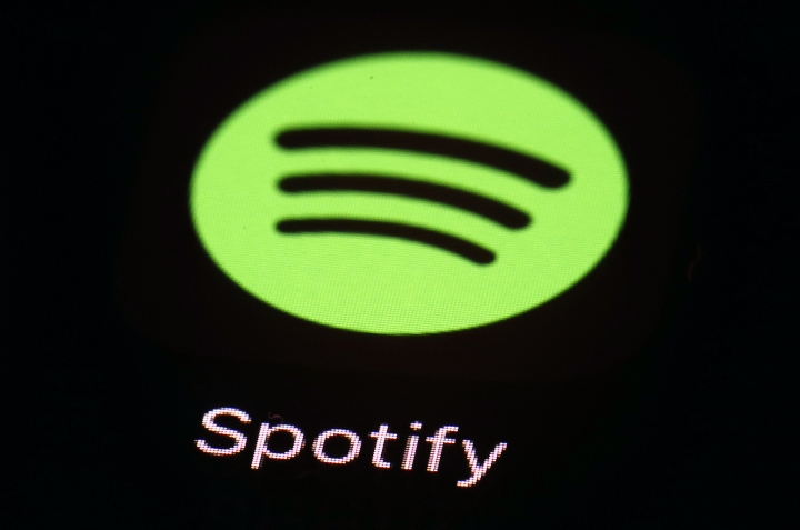 FILE- This March 20, 2018 file photo shows the Spotify app on an iPad in Baltimore. Music site Spotify has complained to European Union regulators about Apple, saying that the U.S. tech giant is abusing its dominant position in music streaming and hurting competition. Spotify founder Daniel Ek said Wednesday, March 13, 2019 that the company has filed a formal complaint with the executive European Commission against Apple. (AP Photo/Patrick Semansky, File)