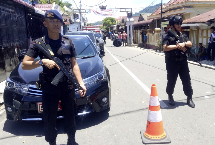 Police officers stand guard near the house of an Islamic militant in Sibologa, North Sumatra, Indonesia, Wednesday, March 13, 2019. The wife and child of an arrested Islamic militant who was plotting attacks in the Indonesian capital have died in an explosion during a siege of their home in North Sumatra, the national police chief said Wednesday.(AP Photo)