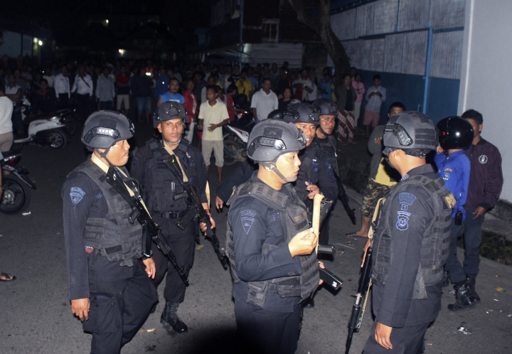 Police officers stand guard near the house of an Islamic militant in Sibologa, North Sumatra, Indonesia, Wednesday, March, 13, 2019. The wife and child of an arrested Islamic militant who was plotting attacks in the Indonesian capital have died in an explosion during a siege of their home in North Sumatra, the national police chief said Wednesday.(AP Photo)