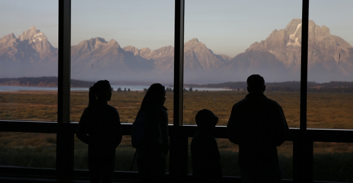 FILE - In this Aug. 28, 2016 file photo visitors watch the morning sun illuminate the Grand Tetons from within the Great Room at the Jackson Lake Lodge, in Grand Teton National Park, north of Jackson Hole, Wyo. Grand Teton National Park in western Wyoming seeks thoughts from the public on plans for a new network of cell towers amid questions about how the National Park Service balances public safety with the experience of wilderness. The park currently has two cell towers as part of a system built piecemeal-fashion, with some fiber-optic lines buried without conduit and poorly mapped. (AP Photo/Brennan Linsley,File)