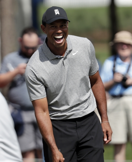 Tiger Woods laughs after putting on the fifth hole during a practice round at The Players Championship golf tournament, Wednesday, March 13, 2019, in Ponte Vedra Beach, Fla. (AP Photo/Lynne Sladky)