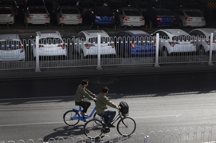 People ride bicycles past new Honda cars stored underneath an overpass in Beijing, Thursday, March 14, 2019. The downturn in China's auto market worsened in January and February as an economic slowdown and a tariff fight with Washington chilled demand in the industry's biggest global market. Sales of SUVs, minivans, and sedans plunged 17.5 percent from a year earlier to 3.2 million SUVs, minivans and sedans in the first two months of 2019, according to an industry group, the China Association of Auto Manufacturers. (AP Photo/Andy Wong)