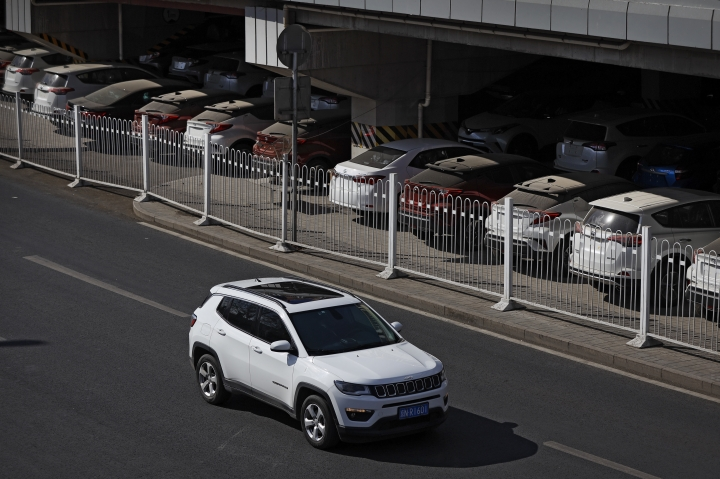 An SUV moves past dust-covered new Toyota cars stored underneath an overpass in Beijing, Thursday, March 14, 2019. The downturn in China's auto market worsened in January and February as an economic slowdown and a tariff fight with Washington chilled demand in the industry's biggest global market. Sales of SUVs, minivans, and sedans plunged 17.5 percent from a year earlier to 3.2 million SUVs, minivans and sedans in the first two months of 2019, according to an industry group, the China Association of Auto Manufacturers. (AP Photo/Andy Wong)