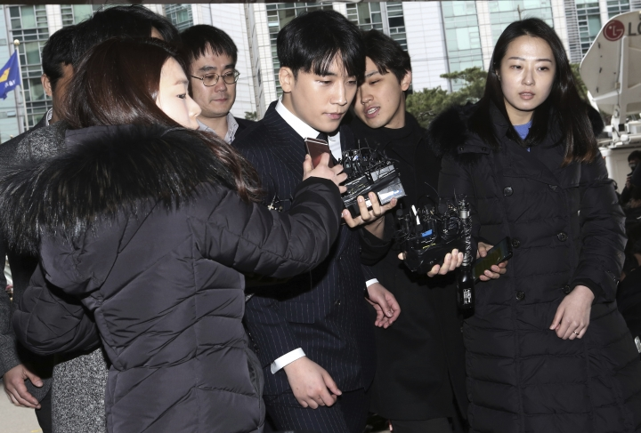 Seungri, center, member of a popular K-pop boy band Big Bang, arrives at the Seoul Metropolitan Police Agency in Seoul, South Korea, Thursday, March 14, 2019. After their stunning retirement announcements, two K-pop stars including a member of the superstars Big Bang are facing police questioning over a series of interlocking scandals that have roiled South Korea for weeks. (AP Photo/Ahn Young-joon)
