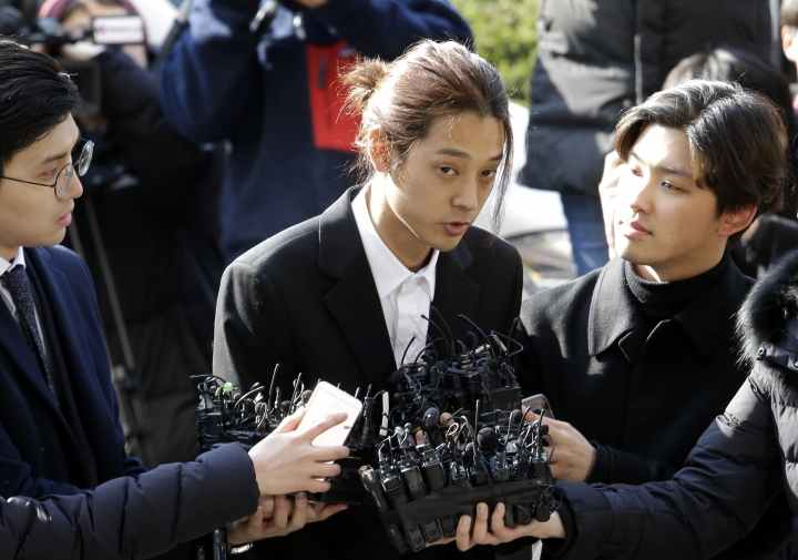 K-pop singer Jung Joon-young, center, speaks upon his arrival at the Seoul Metropolitan Police Agency in Seoul, South Korea, Thursday, March 14, 2019. Police have alleged Jung secretly filmed himself having sex with about 10 women and shared the footage with friends by a mobile messenger app. (AP Photo/Ahn Young-joon)