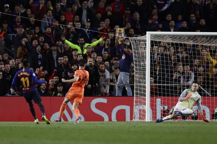 Barcelona forward Ousmane Dembele, left, scores his side's fifth goal during the Champions League round of 16, 2nd leg, soccer match between FC Barcelona and Olympique Lyon at the Camp Nou stadium in Barcelona, Spain, Wednesday, March 13, 2019. (AP Photo/Manu Fernandez)