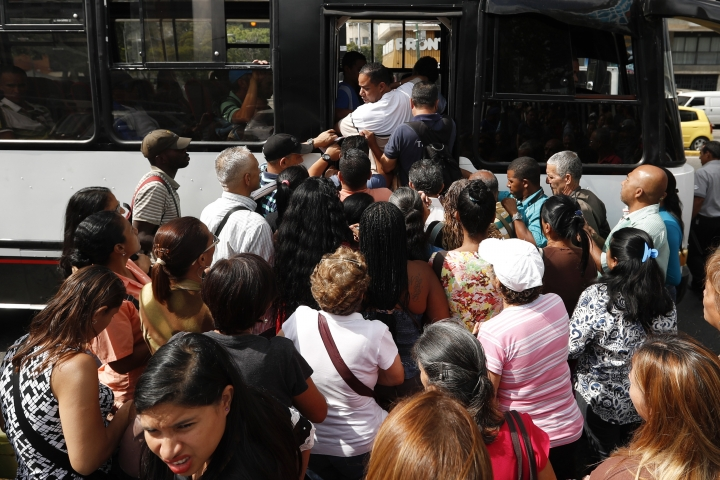 Passengers scramble to board a bus in Caracas, Venezuela, Thursday, March 14, 2019. With long lines at the stops of public transport and crowds of people at the entrance of some banking agencies, Venezuelans returned to activity on Thursday after four days of paralysis as a result of the biggest blackout in the country's history. (AP Photo/Eduardo Verdugo)