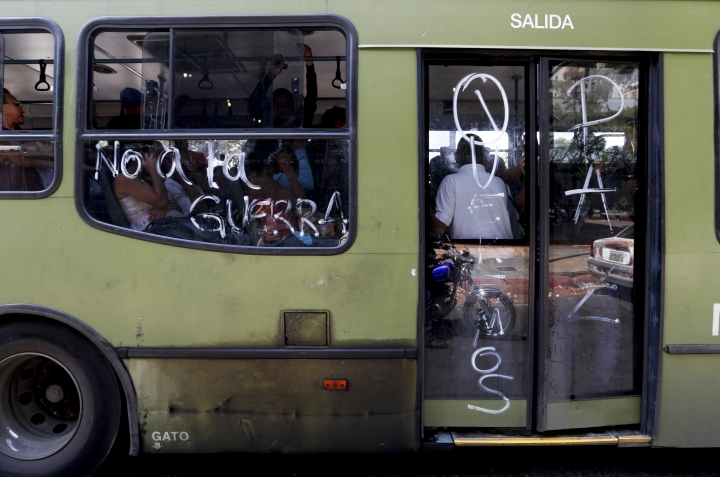 "Passengers ride on a bus with messages scrawled on it that read in Spanish ""No to war,"" and ""We want peace,"" in Caracas, Venezuela, Thursday, March 14, 2019. With long lines at the stops of public transport and crowds of people at the entrance of some banking agencies, Venezuelans returned to activity on Thursday after four days of paralysis as a result of the biggest blackout in the country's history. (AP Photo/Eduardo Verdugo)"