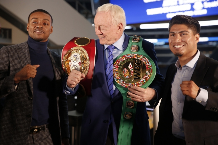 Boxers Errol Spence Jr., left, and Mikey Garcia, right, adorn Dallas Cowboys owner Jerry Jones with their championship belts during a press conference Tuesday, Feb. 19, 2019 in Arlington, Texas. The pair are slated to square off on Saturday at AT&T Stadium for Spence's IBF welterweight title. (Rose Baca/The Dallas Morning News via AP)