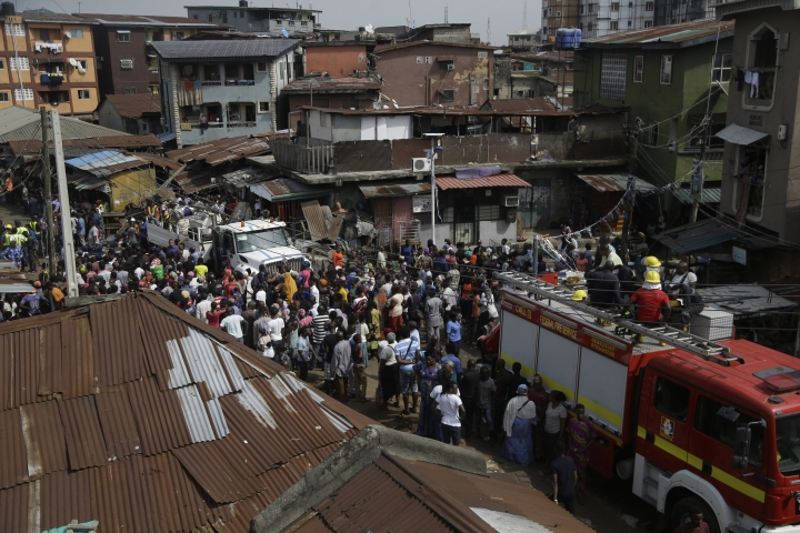 People gather near the scene of a collapsed building in Lagos, Nigeria, Thursday March 14, 2019. Search and rescue work continues in Nigeria a day after a building containing a school collapsed with scores of children said to be inside. A National Emergency Management Agency spokesman late Wednesday said 37 people had been pulled out alive, with eight bodies recovered from the ruins. An unknown number remain missing. (AP Photo/Sunday Alamba)