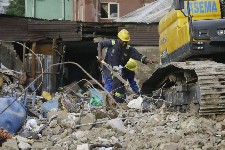 Emergency workers attend the scene after a building collapsed in Lagos, Nigeria, Thursday March 14, 2019. Search and rescue work continues in Nigeria a day after a building containing a school collapsed with scores of children said to be inside. A National Emergency Management Agency spokesman late Wednesday said 37 people had been pulled out alive, with eight bodies recovered from the ruins. An unknown number remain missing. (AP Photo/Sunday Alamba)