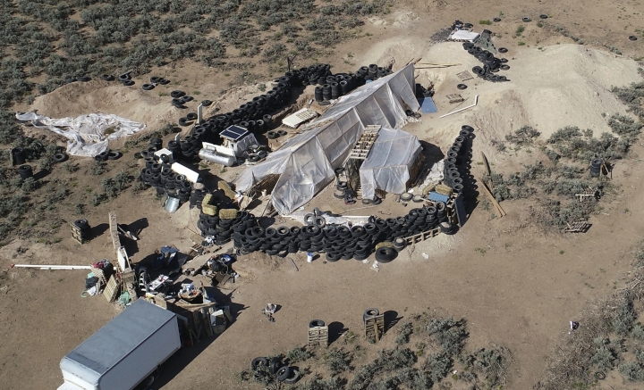 FILE - This Aug. 10, 2018, file photo shows a ramshackle compound in the desert area of Amalia, N.M. The five men and women found living in a ramshackle compound in northern New Mexico where a boy was found dead last year have been indicted on federal charges related to terrorism, kidnapping and firearms violations. The U.S. attorney's office in New Mexico announced the superceding indictment Thursday, March 14, 2019. (AP Photo/Brian Skoloff, File)